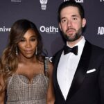 Serena Williams wears a multi-patterned dress and stands with Alexis Ohanian, in a black tux, on the red carpet