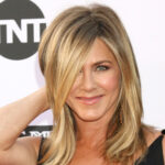 Jennifer Aniston in a black dress smiling at the camera at a red carpet event.