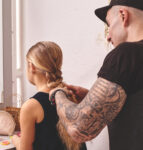 Father braiding his daughter's hair in the mirror