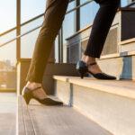 Woman wearing low heels walking up a flight of stairs.