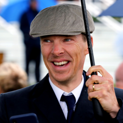 Benedict Cumberbatch smiles, holding an umbrella and wearing a gray cap