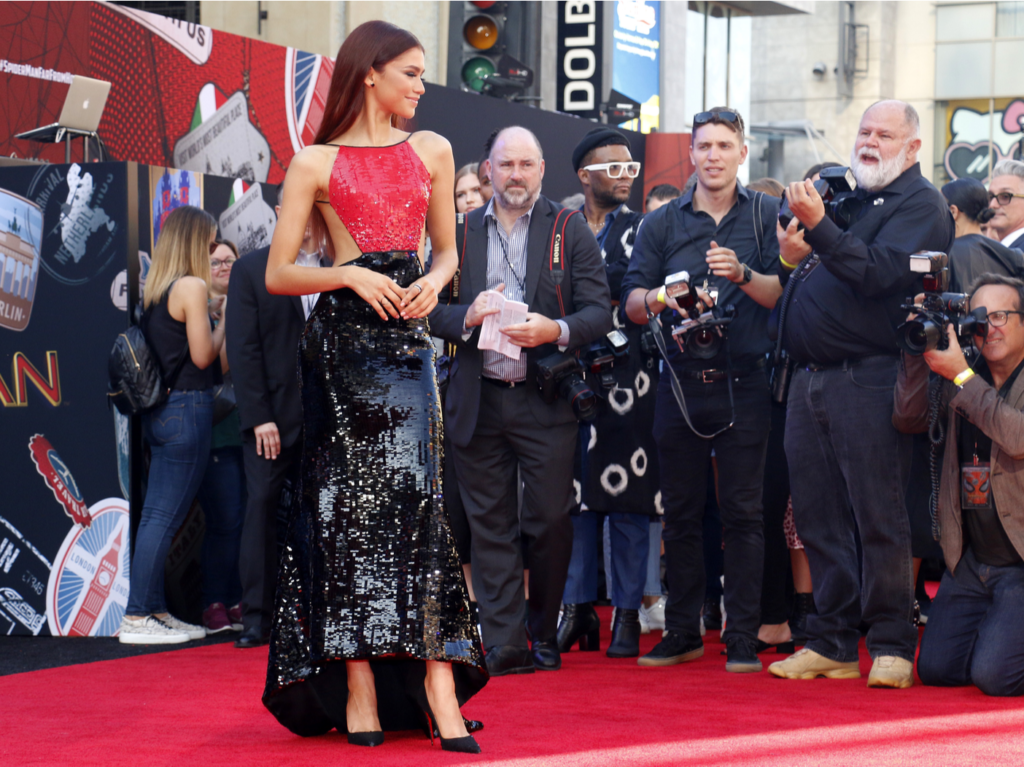 Zendaya stands on the red carpet in a red top and black sequined skirt