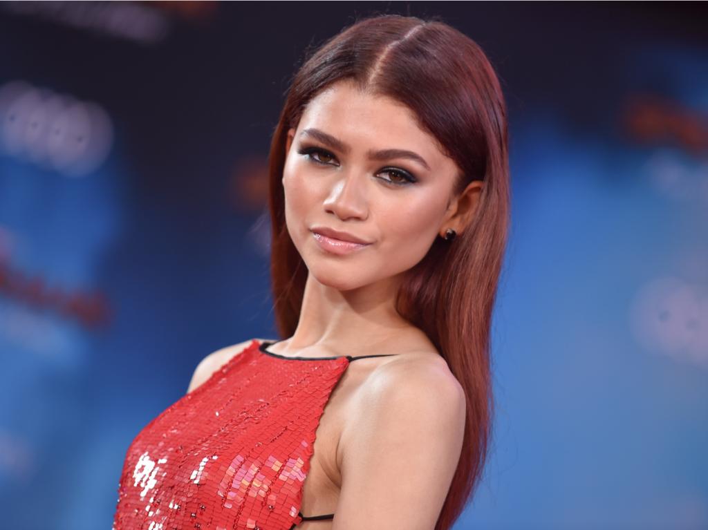 Zendaya looks at the camera, wearing a slinky red dress