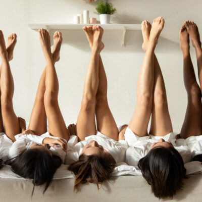 Women laying on a bed with their legs in the air.
