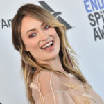 Olivia Wilde smiling widely, while looking over her right shoulder.