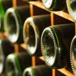 Bottom of wine bottles peeking out of a wooden cellar.