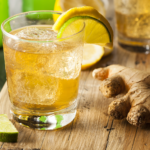 a cup of ginger ale with a lime on the rim