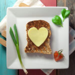 Heart shaped cheese or butter on a piece of whole grain bread.
