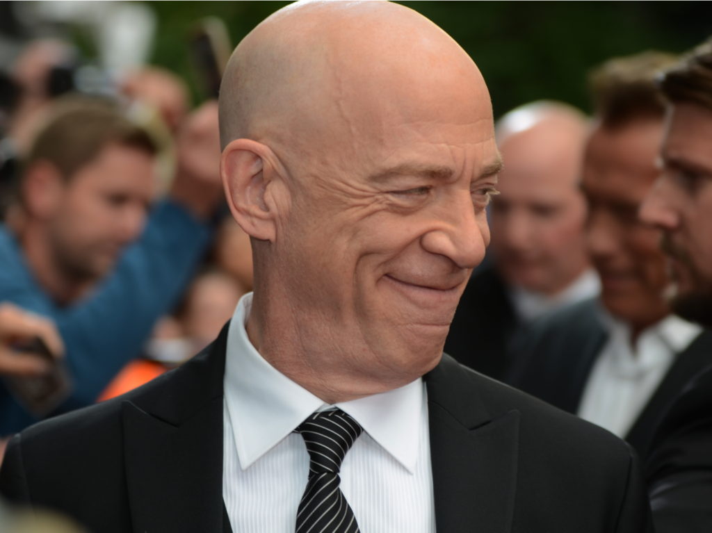 J.K. Simmons smiles at the crowd wearing a sharp-looking tuxedo