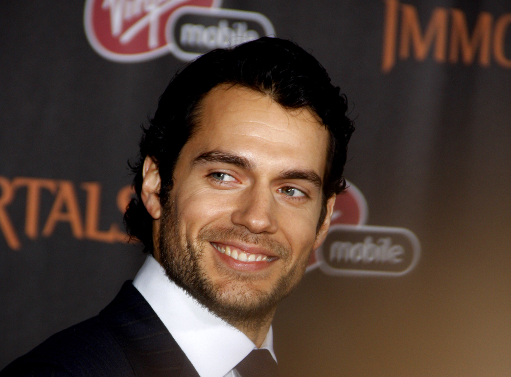 Close-up of Henry Cavill smiling in a tuxedo at a red carpet event.