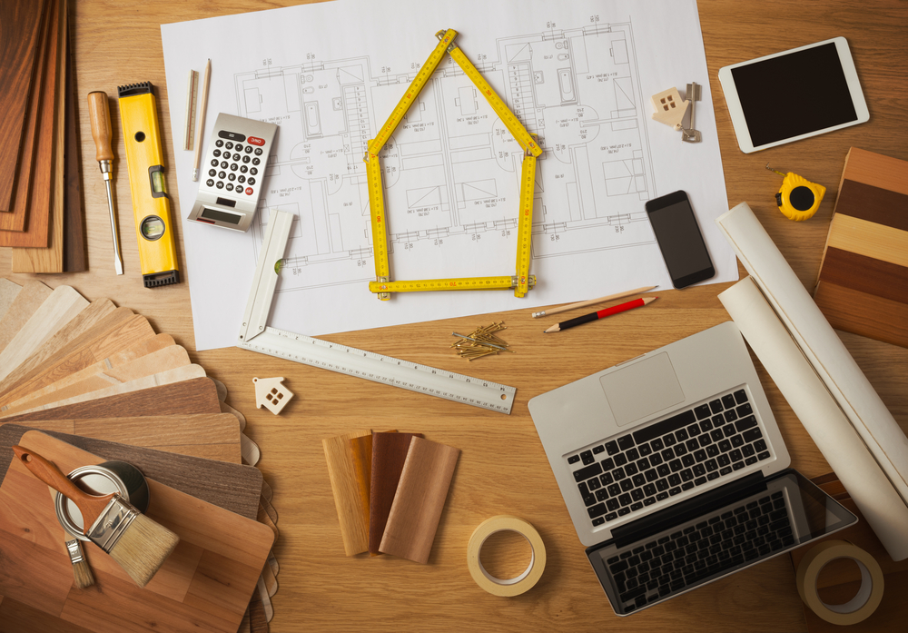 Top view of a workspace with home improvement plans and tools.
