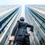 Businessman looking up at tall office buildings.