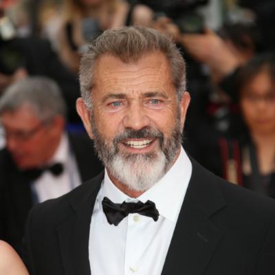 Mel Gibson smiles on the red carpet wearing a black tuxedo