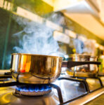 Pots with steam on a gas range with a woman chopping food in the background.
