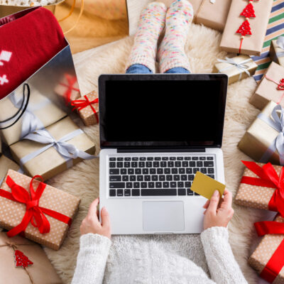 Woman with a laptop surrounded by wrapped holiday gifts.