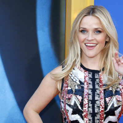 Reese Witherspoon waves at the camera in a patriotic outfit at a film premiere.