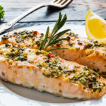 Cooked salmon on a plate with herbs and a lemon slice.