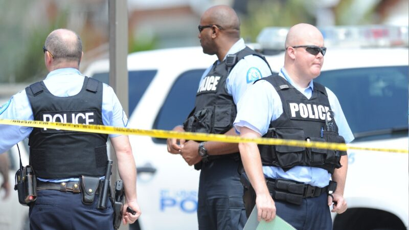 Three St. Louis police officers stand together while wearing bulletproof vests behind yellow caution tape
