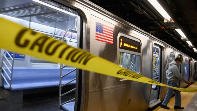 A photo of a New York subway with yellow caution tape in the foreground