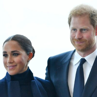 Meghan Markle, in a dark top and blue jacket, stands with Prince Harry, in a blue suit, while visiting New York