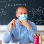 A male teacher wearing a blue shirt and a face mask sits at a desk in a classroom