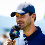 Tony Romo speaking into a microphone