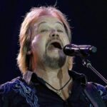 Travis Tritt wears a dark shirt and holds a guitar as he performs onstage