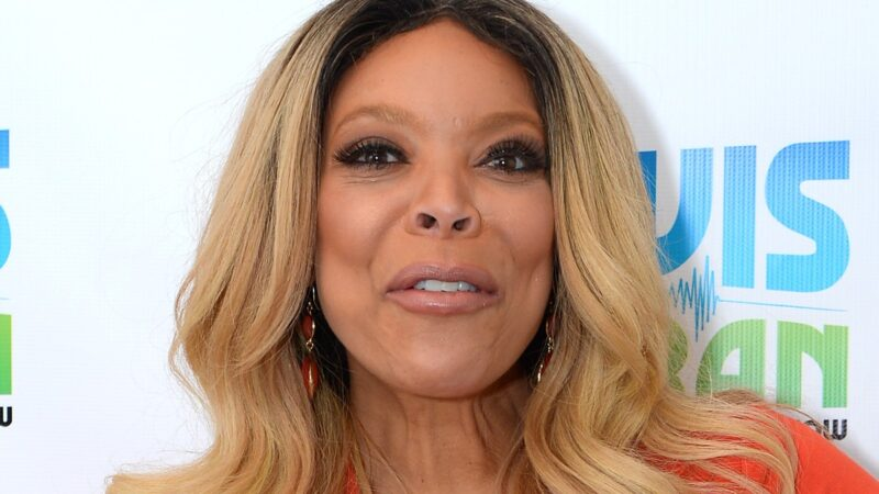 Wendy Williams wears an orange dress against a white background with blue and green letters