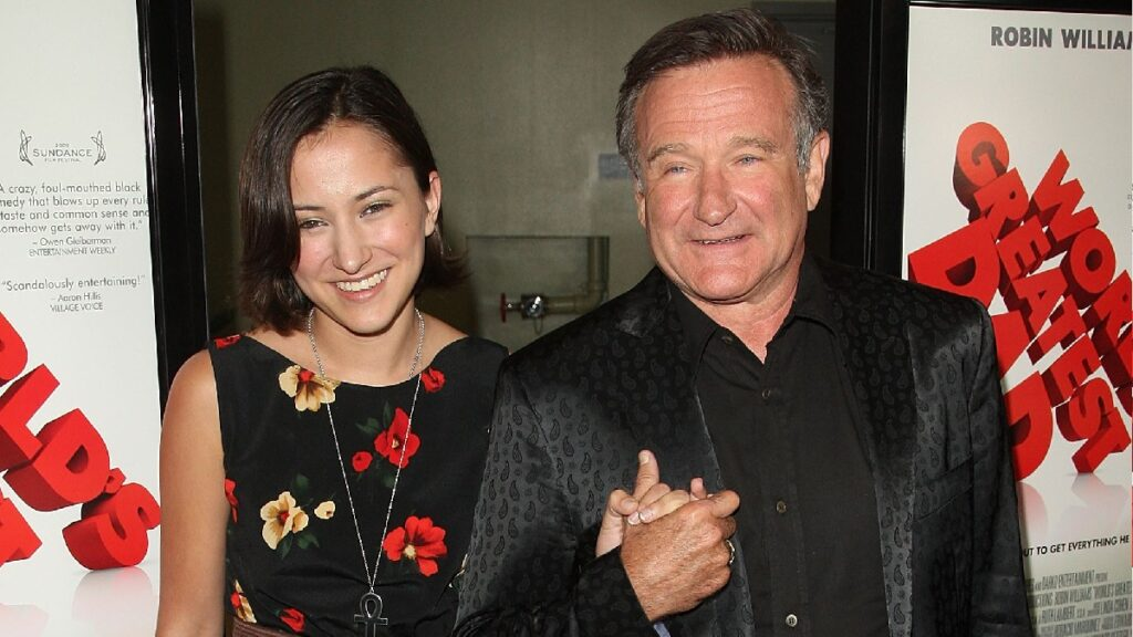 Zelda Williams, in a black dress with colorful flowers stands with Robin Williams, in a black suit, on the red carpet